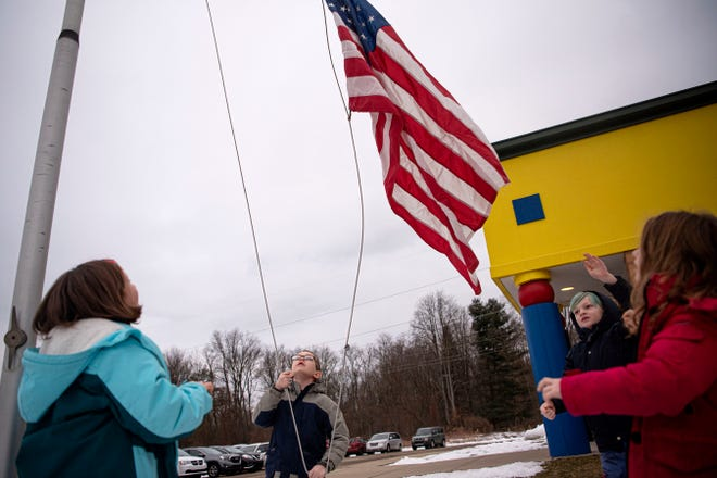 Second grade students Liam Howe, Caroline Kurtz, Sabastian Game-Brown and Molly Ferrell raise the American flag at Pennfield's Purdy Elementary on Wednesday, Jan. 29, 2020 in Battle Creek, Mich.