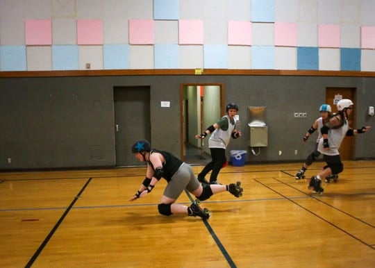 Co-captain Alex Landing, known as Velvet Hammer in roller derby, takes a fall during a practice jam where she's playing the jammer.