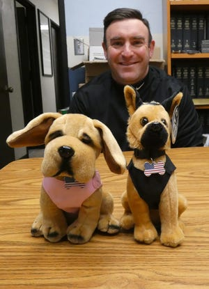 Bucyrus Police Department Capt. Neil Assenheimer displays the plush animal versions of the department's two K-9 officers, Ellie and Harvey.