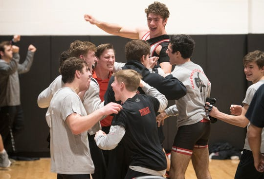 Haddonfield High School's wrestling coach Eric Hamrick celebrates with his wrestlers after Haddonfield defeated Collingswood, 40-26, at Haddonfield High School on Wednesday, January 29, 2020.