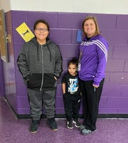 (L-R) Robbie Harris, Ronnie Mango and Ashton Boggs stand inside the Unioto Elementary School gymnasium. Boggs teaches health and wellness to students. In her class, Harris learned the Heimlich maneuver which he used to save his brother's life.