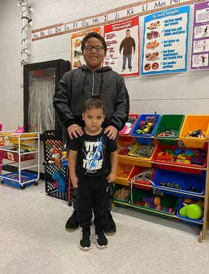 11-year-old Robbie Harris poses with his brother, Ronnie Mango, 4, in the Unioto Elementary School classroom where Harris learned the Heimlich maneuver that he used to save his younger brother's life.