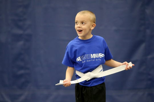 A Club MMA student smiles during an exercise at the Green Township facility.