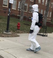In a photograph provided by a Miami University student, a student crosses the Oxford, Ohio, campus Wednesday in a full protective suit and mask. Two Miami students who traveled to China over the January break were in isolation after testing for possible exposure to the 2019 novel coronavirus.