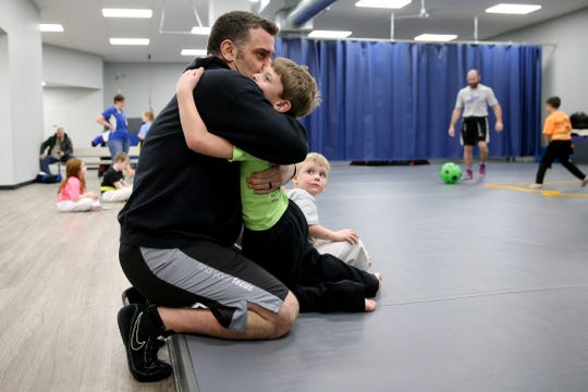 Owner Jeff Robison hugs his son, Stryker, 6, at Club MMA.