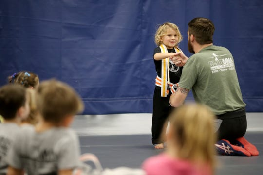 Coach Josh Geers shakes hands with Seraphina Cucura, 4, after she earned an orange belt at Club MMA in Green Township.