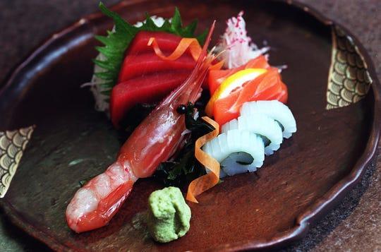Sushi from Jo An. Clockwise from bottom left, sweet shrimp, tuna, Japanese basil, shredded icicle radish, salmon, squid, and wasabi.