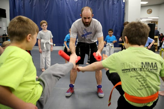 Coach Nik Hoobler-Scherff holds out pool noodles for children to kick during an exercise at Club MMA.