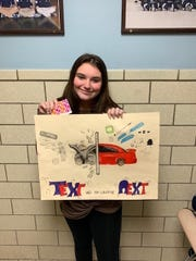 "Alexa Grasso, a sophomore at Arthur L. Johnson High School in Clark with her ""Text and Your Could be Next"" poster."