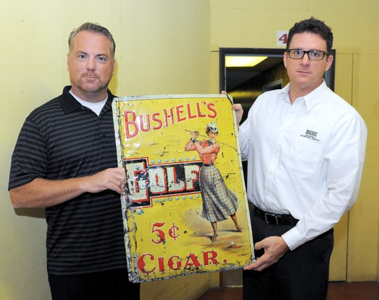 A tin sign for Bushell's Golf Cigars designed and produced at The Novelty Advertising Company held by brothers Thad and Greg Coffman in a Tribune File photo from 2012. Several properties owned by the company, including the main building at 1148 Walnut St. are included in a Feb. 28 sheriff's sale as Home Loans Savings Bank is seeking repayment of more than $1.18 million in debts, including interest, from defaulted loans.