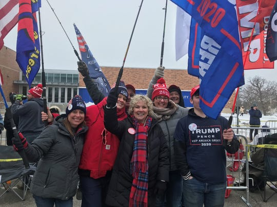 Trump supporters rally together to pump up a chilled crowd outside the Knapp Center on the campus of Drake University.