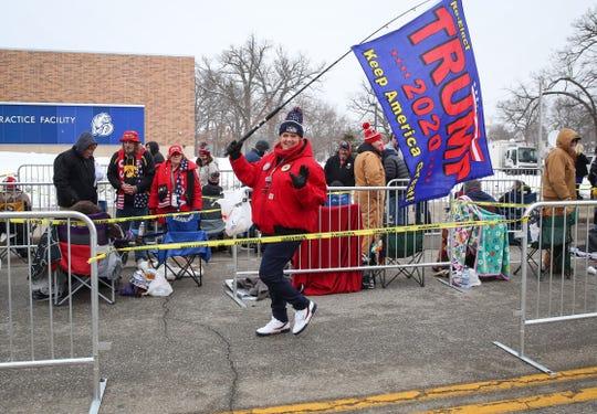 Jaimi Fay of Omaha, Nebraska, carries a flag in support of President Donald Trump outside of the Knapp Center at Drake University in Des Moines.