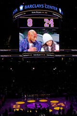 An image of retired Los Angeles Lakers superstar Kobe Bryant, left, and his daughter Gianna is shown on a giant video screen above the arena as his jersey numbers are displayed on the floor along with spotlights for others who perished in the helicopter crash that killed the pair during a pregame tribute before an NBA basketball game between the Brooklyn Nets and the Detroit Pistons, Wednesday, Jan. 29, 2020, in New York. (AP Photo/Kathy Willens)