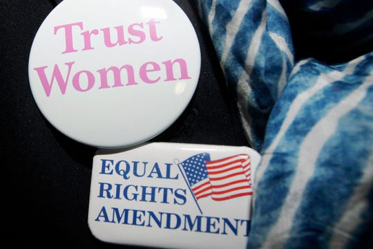 A  woman wears buttons showing her support for the Equal Rights Amendment.