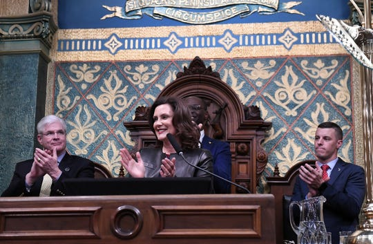 Gov. Gretchen Whitmer with Lt. Gov. Garlin Gilchrist II, behind her, acknowledges some guests, during the State of the State address at the Capitol Building in Lansing, Mich. on Jan. 29, 2020.  She is flanked by Senate Majority Leader Mike Shirkey, left, and Speaker of the House Lee Chatfield, right.