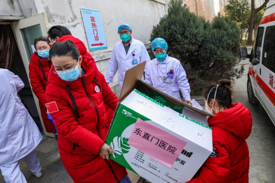 Doctors watch as donated medical supplies from Beijing are unloaded at a hospital in Wuhan in central China's Hubei Province, Thursday.