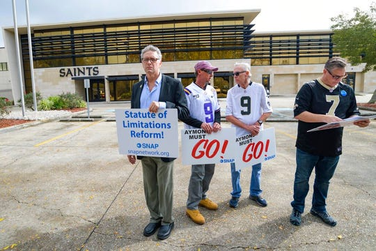 "Members of SNAP, the Survivors Network of those Abused by Priests, including John Gianoli, left, Richard Windmann, John Anderson, and Kevin Bourgeois, hold signs during a conference in front of the New Orleans Saints training facility in Metairie, La., Wednesday Jan. 29, 2020. SNAP is demanding that Gayle Benson, the owner of the NFL Saints and NBA Pelicans, release all emails where the Saints provided public relations assistance to the Catholic Archdiocese of New Orleans regarding clergy sexual abuse cases. The sign ""Aymond Must Go!"" refers to New Orleans Archbishop Gregory Aymond while Gianoli holds a sign asking for statute of limitations reform since he was a child when he was abused and didn't report the abuse till years later."