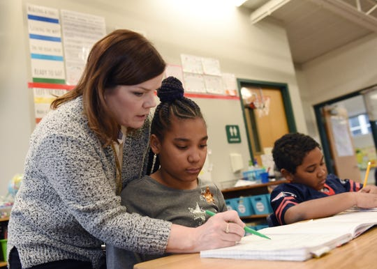 4th grade teacher Roberta Lusk, left, helps Toyoko Collins,10, with her writers workshop assignment.
