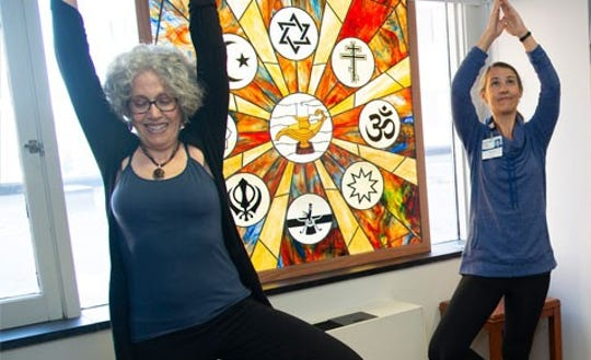 Dr. Ruth Lerman, left, and Lucy Sternburgh extend their arms into a yoga position as part of one class.