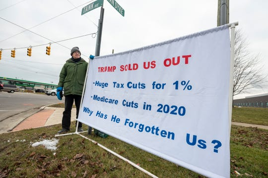 Tom Moran, of Fenton, displays a sign critical of President Donald Trump before a visit from the president at Dana Incorporated, in Warren January 30, 2020.