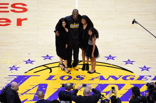 Kobe Bryant stands with his wife Vanessa, left, and daughters Natalia, second from right, and Gianna after an NBA basketball game April 13, 2016.