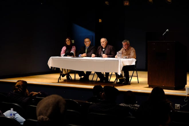 Hani Bawardi (holding microphone), history professor at University of Michigan Dearborn, speaks to community members on how they should articulate responses to the plan at the Arab American National Museum Wednesday.
