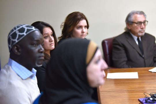 Seated foreground to background are CAIR MI CAIR attorney Amy Doukoure, plaintiffs / former co-workers Aliou Diao and Alicia Dunlap and their attorneys Channing Robinson and Michael Pitt.