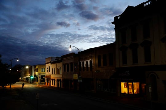 FILE - In this Oct. 28, 2017, file photo the storefront window of a portrait studio is lit up along a downtown street at dusk in Lumberton, N.C.