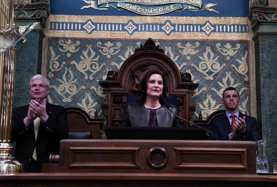 Gov. Gretchen Whitmer acknowledges some guests, during the State of the State address at the Capitol Building in Lansing, Mich. on Jan. 29, 2020.  She is flanked by Senate Majority Leader Mike Shirkey, left, and Speaker of the House Lee Chatfield.