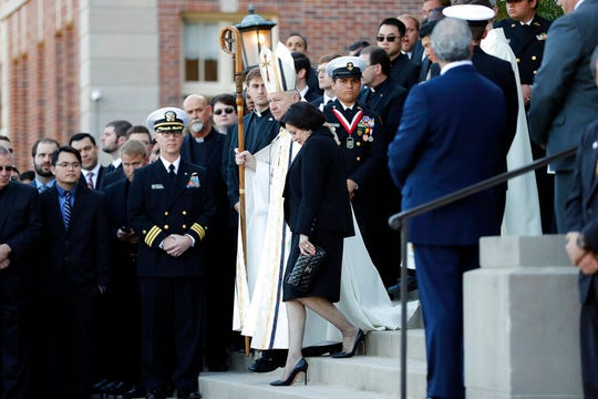 In this March 21, 2018, file photo, Gayle Benson, widow of NFL New Orleans Saints and NBA New Orleans Pelicans owner Tom Benson, walks down the steps to receive his casket with New Orleans Archbishop Gregory Aymond for visitation at Notre Dame Seminary in New Orleans.