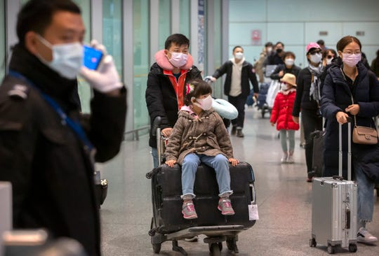 Travelers wearing face masks enter the international arrivals area at Beijing Capital International Airport in Beijing, Thursday.