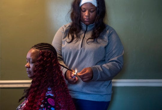 """Bre'Monyaa does her mother, Monya Lewis' hair, at Lewis' boyfriends home in Evansville. """"We're living with her boyfriend right now, and that's gonna go good hopefully,"""" Bre'Monyaa said of their current living situation. """"I'm proud of my mom. We've come so far and we can't fall now."""""""