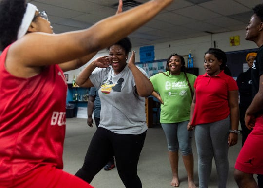 """Blue Diamonds team captain Keasha McCants, 17, left, and Bre'Monyaa Jones, 17, second left, goof for their teammates for a laugh during a Boom Squad practice. """"At home everything is not really too good,"""" Bre'Monyaa said. """"When I come here I be at peace. You know, I come here and have laughs and giggles and all that."""""""