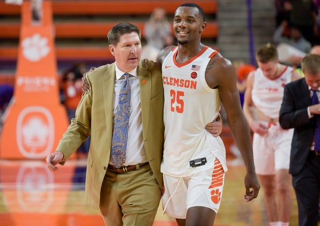 Clemson coach Brad Brownell, heading off the court with Aamir Simms (25), has become the school's all-time winningest coach.