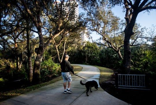 A man walks a dog in a preserved area at Bonita Bay on Thursday Jan. 30, 2020.