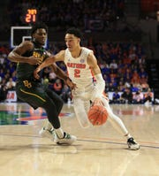 Florida guard Andrew Nembhard (2) dribbles around Baylor guard Davion Mitchell (45) during the first half of a game Saturday, Jan. 25, 2020, in Gainesville, Fla.