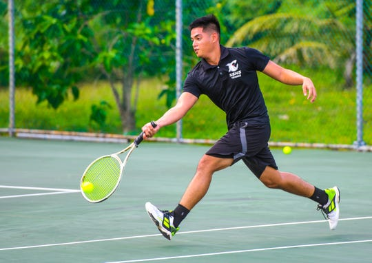 Simon Sanchez High's Roan Carlos scoops a low return while competing in a singles match against the Guam High Panthers at the Ninete Tennis Center in Hagåtña Jan. 30. The Guam High boys won 32-9, while the school's girls team won 32-1. The boys team is now 4-0, while the girls team is 3-0.