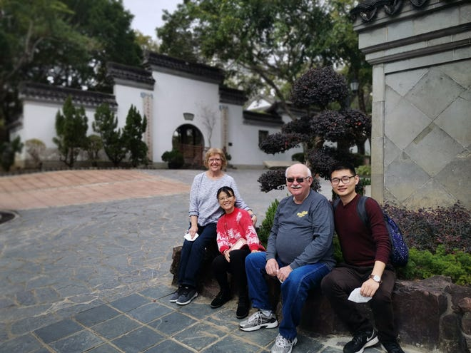 """Seated in a walled park in Hong Kong, (from left) Amy Taylor, Qu Xuejing (or """"Zoe""""), Alan Taylor and Zoe's husband, Wang Wei, pose for a photo during a visit by the Taylors that was abruptly cut short because of the Chinese government's shutting down of tourist destinations in hopes of curbing the transmission of a deadly new form of coronavirus that has spread from central China to a growing swath of the world."""