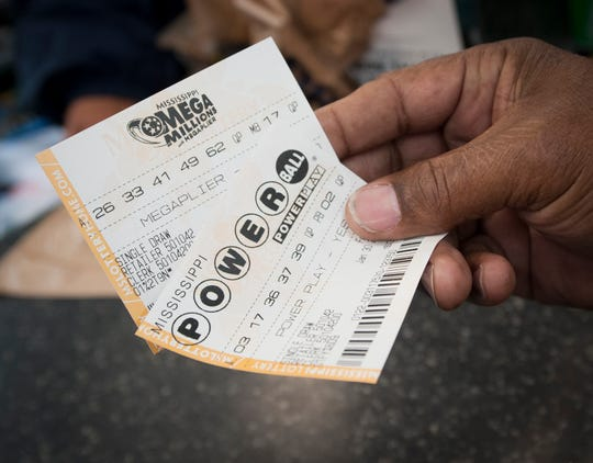 A customer at Sprint Mart in Jackson buys one of each ticket Thursday morning on the first day of ticket sales for Mega Millions and Powerball in Mississippi Jan. 30.