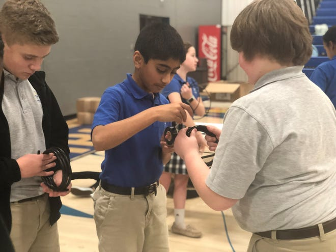 Jackson Christian School students Evan Farrar, Caleb Santhosh, and Ben Patrick measure and cut the supply line for a drip irrigation system to be sent to Zambia during a school project on Wednesday.