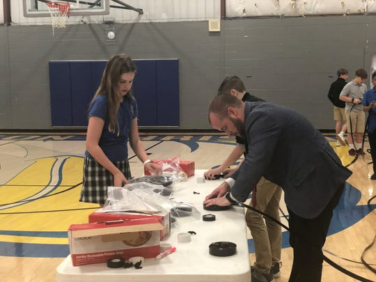 Jackson Christian sixth grader Jenna Quinn and Director of Admissions Blake Beckham work on one part of assembling the irrigation systems.