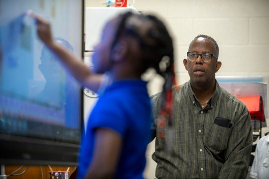 "Jeff Davis watches his students write on a video screen at Lincoln Elementary on Tuesday. ""I try to teach them like they can do it,"" Davis said of his classroom philosophy. ""I push them as hard as I possibly can, not always to the success from everybody."""