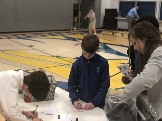 Jackson Christian School students Carter Smith, Brody Smith and Kennedy Ellis write encouragement cards to include in drip irrigation system kits to be shipped to Zambia.