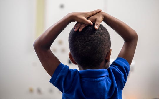 A student puts his hands on his head during Jeff Davis' kindergarten class at Lincoln Elementary in Jackson.