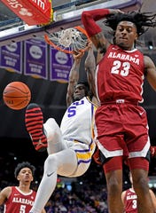 LSU forward Emmitt Williams (5) dunks the ball as Alabama guard John Petty Jr. (23) defends in the first half of an NCAA college basketball game, Wednesday, Jan. 29, 2020, in Baton Rouge, La. (AP Photo/Bill Feig)