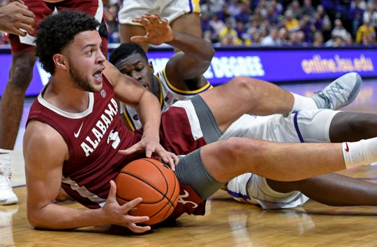 Alabama forward Alex Reese (3) hits the floor while going after a loose ball as LSU forward Darius Days, background, applies pressure in the second half of an NCAA college basketball game, Wednesday, Jan. 29, 2020, in Baton Rouge, La. LSU won 90-76. (AP Photo/Bill Feig)