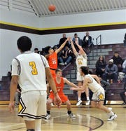 Berne Union's Brock Unger shoots a 3-pointer over Heath's Keylan Williams during the Bulldogs' 57-49 win over the Rockets Wednesday night.