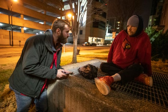 5:25 AM  Joe Newland, left, a volunteer for Coalition for the Homeless' 2020 census, talks with Owen Hogan, who was sleeping on a heating vent on Abraham Flexner Way on Jan. 30, 2020.