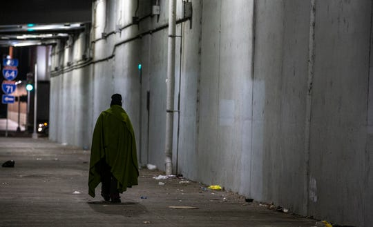 A homeless man walks along Jefferson Street under the I-65 overpass with a blanket around him. Volunteers canvased the area for the 2020 census of the homeless on Jan. 30, 2020.