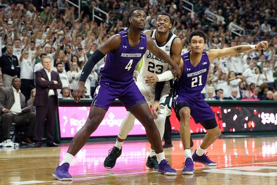 Jan 29, 2020; East Lansing, Michigan, USA;  Northwestern Wildcats forward Jared Jones (4) and Michigan State Spartans forward Xavier Tillman (23) and Northwestern Wildcats forward A.J. Turner (21) fight for position during the second half a game at the Breslin Center. Mandatory Credit: Mike Carter-USA TODAY Sports